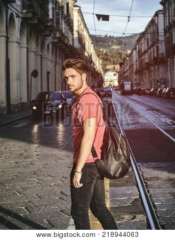 One handsome young man in urban setting in European city, Turin in Italy. Looking at camera, walking