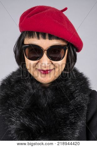 Closeup Shot of an Asian Woman with Short Hair Wearing a Red Beret, Pair of Cool Sunglasses and a Black Wool Coat with a Faux Fur Collar