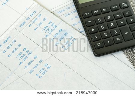 Financial office salary tax calculation with salary revenue slips with numbers and calculator put on table. poster