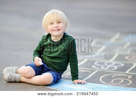 Cute little boy drawing hopscotch using chalk on asphalt. Child playing hopscotch on playground outdoors on a sunny day. Activities for toddler kids.