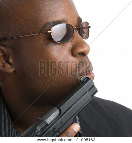Black man blowing across the barrel of a gun