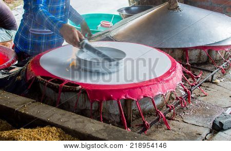 Cooking rice pancakes drying on the sun in the rice noodles factory, Can Tho, Mekong Delta , South Vietnam