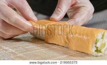 Professional sushi chef preparing roll at commercial kitchen. Cook puts the salmon on roll. Japanese cuisine recipes close-up