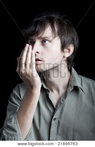 Man checking his breath for odor