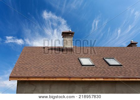 New roof with skylight asphalt roofing (shingles) and chimney. Roof with mansard windows .