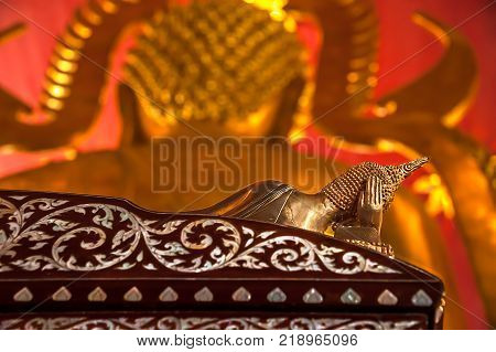 STILL LIFE OF RECLINING BUDDHA STATUES. Bronze Buddha statue in reclining posture with right hand supporting the head, lying on a rosewood bed with pearl inlay. In front, there is another Buddha statue out of focus.