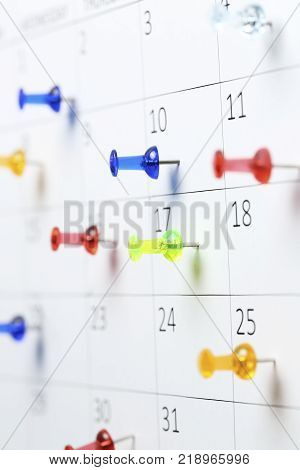 colorful pushpins on white calendar clsoe up shallow dof