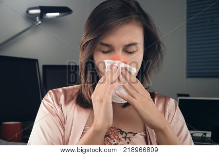Asian women in satin nightwear feeling unwell and sneeze on desk at home. People Caught Cold and flu.