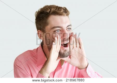 Closeup portrait of handsome content young man shouting loud holding hands near to mouth. Businessman announcing good news. Announcement concept