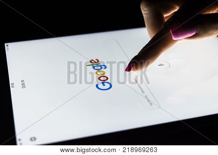 Sankt-Petersburg Russia December 20 2017: A woman's hand is touching screen on tablet computer iPad Pro at night for searching on Google search homepage. Google is the most popular Internet search