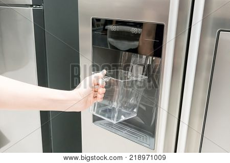 Closed Up Woman Hand Holding Empty Plastic Container Under The Ice Maker Of Refrigerator.