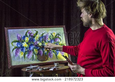 A man bearded artist in a dark sweater draws an artistic brush painting flowers still life on easer in the studio