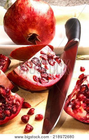 sliced pomegranate and big kitchen knife on wooden board