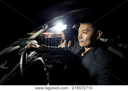 Asian man driving with a black african female date in a car. They look like they are heading to a nightclub for clubbing nightlife. The image depicts interracial relationships and lifestyle.