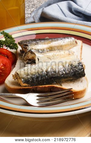 sardines on toast and with tomato and fork on a plate