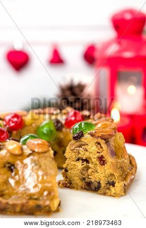 Glazed colorful Christmas fruitcake topped with almonds and glace cherries on white platter with candles and decoration items in background