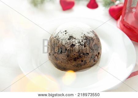 Traditional Christmas or plum pudding with white powder icing sugar on white plate