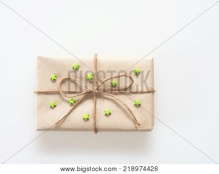 A present or gift box wrapped by rough brown recycled paper and tied with brown hemp rope as ribbon with green rubber star isolated on white background with concept of green and environment friendly