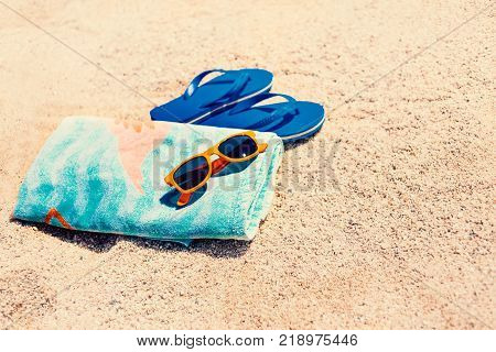 Blue sandal flip flop sun glasses and towel on yellow sand. Summer fun time and accessories on the beach summer vacations copy space