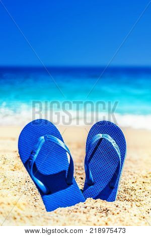 Summer fun time and accessories on a sand on the beach. Blue sandal flip flop on the white sand with blue sea and sky in summer vacations copy space