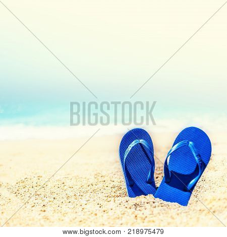 Summer holiday beach background with flip flops on a tropical beach. Slippers from a sand on a beach funny concept