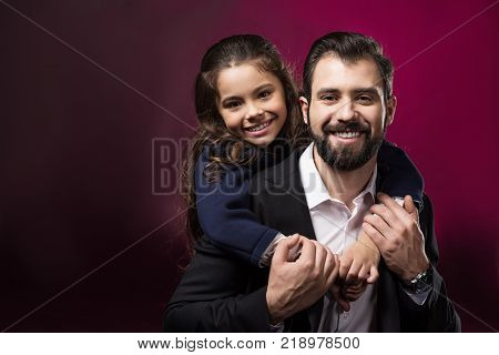 daughter hugging father from back and they looking at camera on burgundy