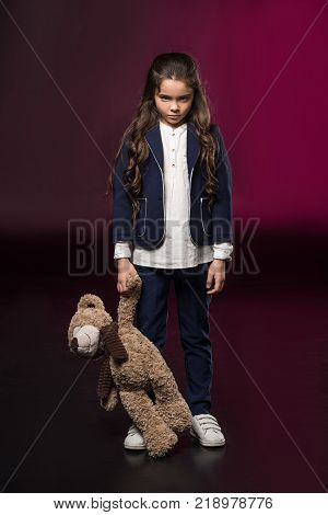 angry kid standing and holding teddy bear on burgundy