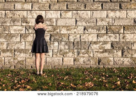 A young girl stands with her back hugging herself with her hands behind her shoulders against the background of a stone wall yellow leaves lie on the green grass