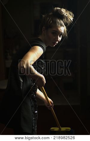 Adorable Brunette Girl in Black Dress is Cleaning House with Mop After Party. Close-up Portrait