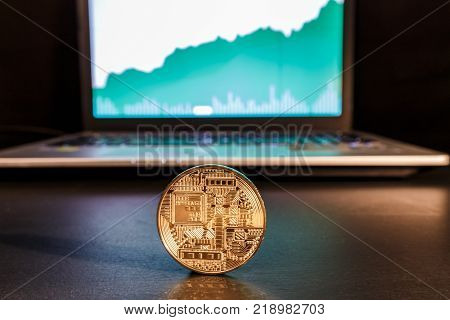 ICO - The initial concept of coin placement for the funding startup projects. In the image of a laptop with a review of quotations and rating ICO. In the center is a gold coin of e-currency as a symbol of new technologies