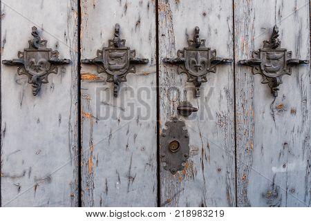metal embellishments on a weathered painted wood door, Salamanca, Spain
