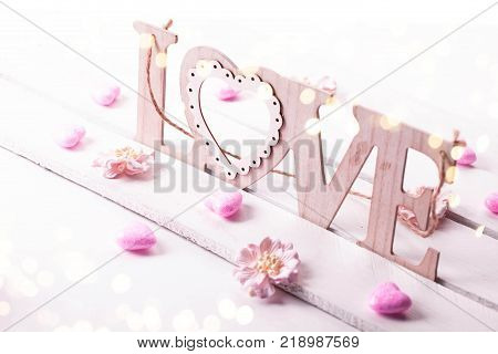 Valentines Day background with wooden word love and hearts