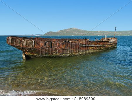 AN OLD RUSTIC SHIP THAT HAS RUN AGROUND