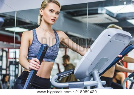 beautiful sportive woman working out on elliptical machine at gym