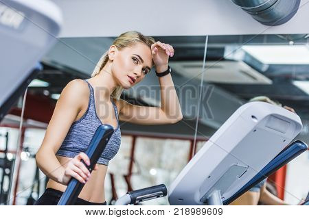 exhausted sportive woman working out on elliptical machine at gym