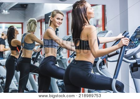 young athletic women working out on elliptical machines at gym
