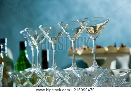 Close-up of glancy, perfectly polished, clear martini glasses, standing on the blue background. There are alcohol bottles and different desserts on the background.