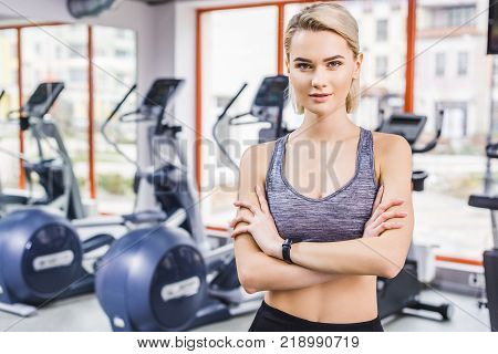 young attractive woman standing with crossed arms at gym in front of elliptical machines