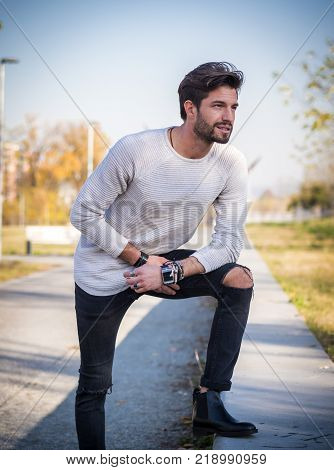 One handsome young man in urban setting in European city park, standing