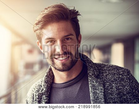 One handsome young man in urban setting in European city, standing, smiling and looking at camera