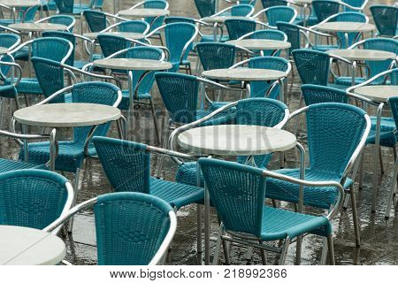 unoccupied cafe chairs and tables lined up in San Marco square in the rain, Venice, Italy