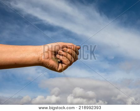 Feminine hand with sand falling down, against the blue sky with white clouds
