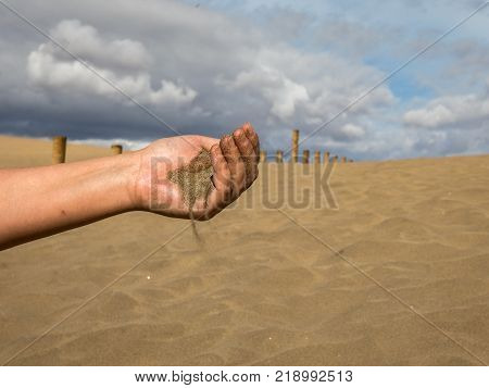 Female hand with sand against the Dunes of Maspalomas with blue sky and clouds in the background, in Gran Canaria, Spain