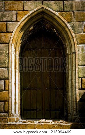 An old medieval wooden door with a studded iron frame