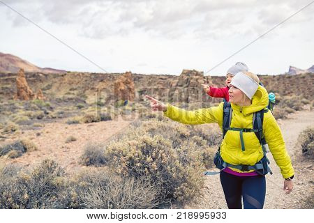 Happy mother with little boy travelling in backpack. Hiking adventure with child on autumn family trip in mountains. Vacations journey with infant carried on back weekend travel in Tenerife Spain.