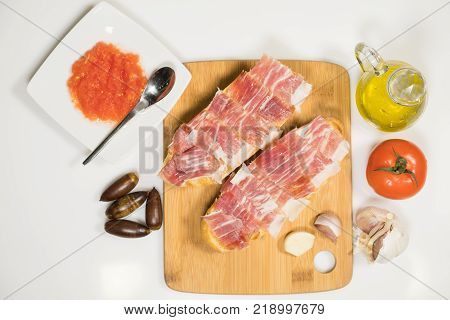 Mediterranean breakfast of homemade bread toasts with natural tomato sauce and acorn fed Iberian ham with extra virgin olive oil and fresh garlic