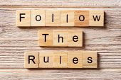 Follow The Rules word written on wood block. Follow The Rules text on table concept. poster