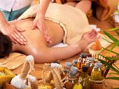 Young woman getting massage in bamboo spa. poster