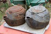 A set of two iron pots sitting together at a flea market. poster