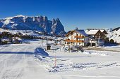 Winter panorama of italian ski resort with background of Seiser Alm Alpe di Siusi a high altitude alpine meadow in Dolomites with Langkofel and Plattkofel mountains under snow South Tyrol Italy. poster